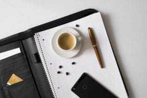 מחברת עם כוס קפה עט וטלפון